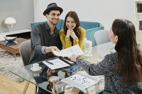 Couple signing sales contract in furniture store