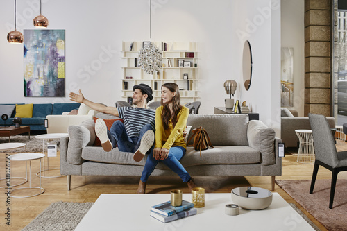 Couple In Modern Furniture Store Testing Couch Being Happy