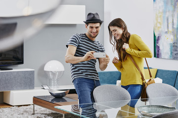 Couple in furniture store looking at dining table, taking pictures with smart phone