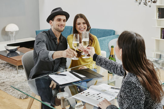 Couple celebrating sales contract in furniture store