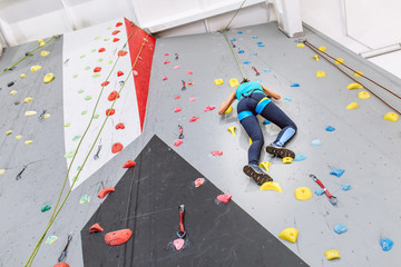 Young woman climbing up on practice wall at indoors gym, rear view