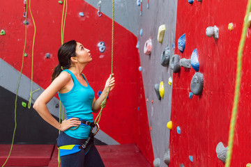 Young woman with belay rope practicing at rock-climbing on a artificial climb wall indoors