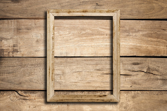 Old picture frame on wood wall.