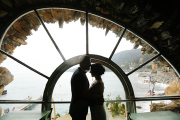 Groom and bride silhouette near a window to the sea
