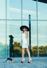 Fashion style elegant woman in white dress and hat posing outdoors