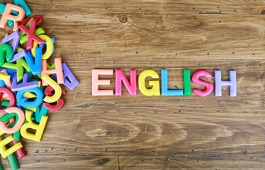 "The colorful word ""ENGLISH"" next to a pile of other letters over the old wood board"