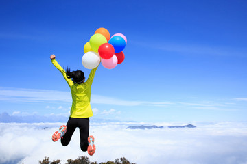 Young woman with colorful balloons jumping on mountain peak