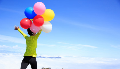 Young woman with colorful balloons running on mountain peak