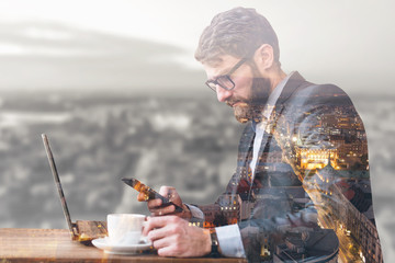 Double exposure of a businessman using phone and laptop with city