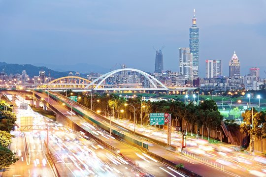 Night scenery of Taipei City, with Taipei 101 Tower in XinYi District, downtown area with arch bridges and car trails on Dike Avenue ~ Romantic cityscape of Taipei at dusk by riverside (long exposure)