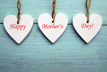 Happy Mother's Day concept.Decorative white wooden hearts on a blue rustic wooden background.