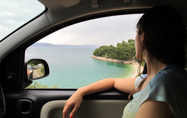young woman looking through the window car to a beach in Croatia
