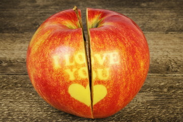 Cut in half apple with an inscription I love you on wood
