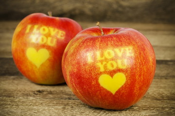 Two apples with an inscription I love you on wood