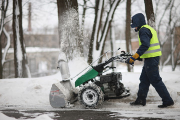 A man cleans the track park snow machines