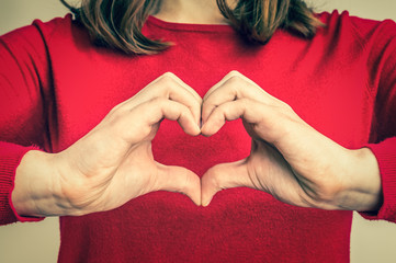 Female hands showing sign of heart - retro style