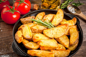 Fried potatoes in a rural style, with spices, rosemary and fresh tomatoes. On rustic pan, on a wooden table, close view copy space