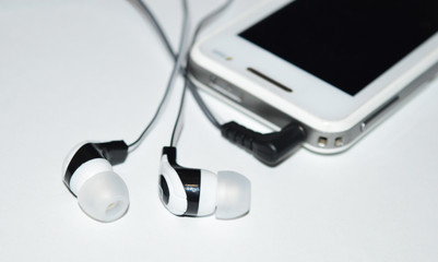 Черно-белые наушники соединены с смартфоном и лежат на белом фоне.