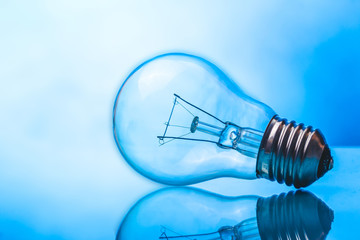 Light bulb on blue glossy reflective glass surface.