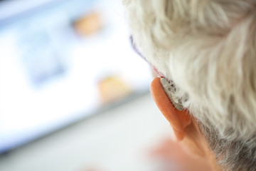 Senior wearing hearing aid in her ears in front a laptop