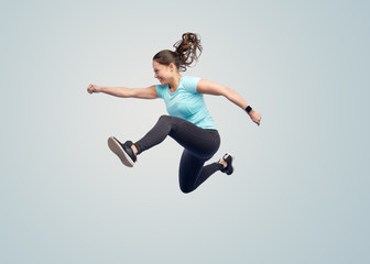 happy smiling sporty young woman jumping in air
