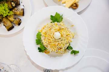 Russian festive salad with chicken and cheese on restaurant table
