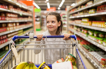 girl with food in shopping cart at grocery store