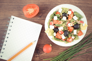 Vintage photo, Fresh greek salad with vegetables and notepad for writing notes, healthy nutrition