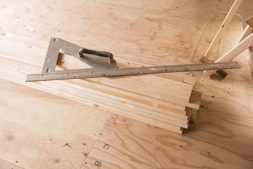 住宅の新築工事現場に置かれた丸鋸ガイド定規と木材