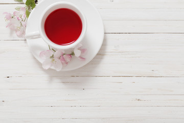 Red tea with flowers on white wooden background