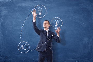 Businessman on blue chalkboard background manipulating white see-through icons that are connected with dash lines.