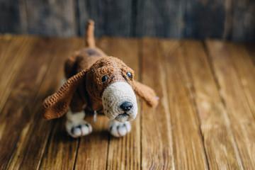 Knitted dog Basset Hound isolated on wooden background.