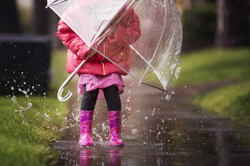 A young girl is playing in the much needed California rain. Wall mural