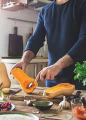 Man preparing healthy food of squash on wooden table