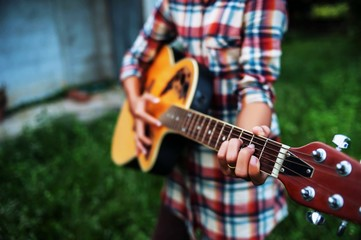 Young hipster woman playing guitar to relaxing on his holiday, enjoy with natural and fresh air.