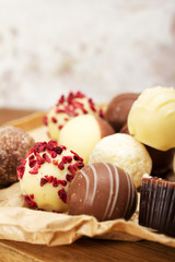 Selection of delicious chocolates on a rustic background