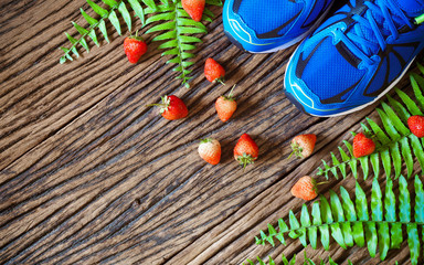 Fitness, healthy eating and active lifestyles Concept,  sport shoes and strawberries on grunge wood background. top view with copy space for text.