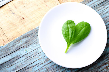 Fresh Baby spinach heart shape leaf on white plate, blue wooden background. Top view with copy space. Love, Healthy, Ecology concept