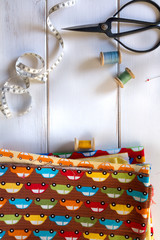 Colorful fabrics with vintage scissors, pins, measuring tape and rolling cotton threads on white wooden table