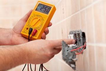 Electrician hands checking voltage in a partially mounted electrical socket - closeup