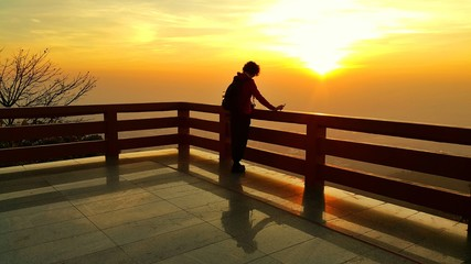 Silhouette of a short curly hair asian woman looking at dramatic sunrise landscape in the morning  at view point balcony of Wat Pra That Doi Suthep, Chiang Mai, Thailand