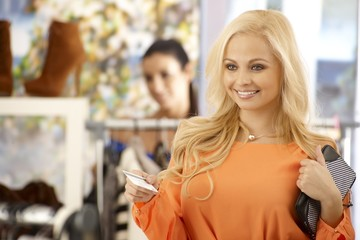 Beautiful blonde female paying by credit card