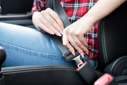 Woman fastening seat belt in car