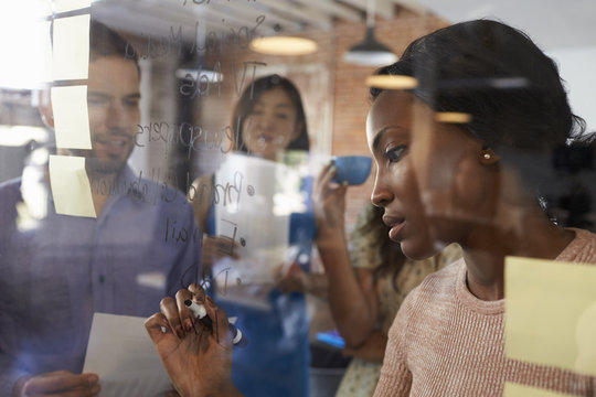 Businesswoman Writing Ideas On Glass Screen During Meeting