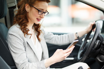 Attractive red hair  businesswoman typing message on the phone while waiting in the car.