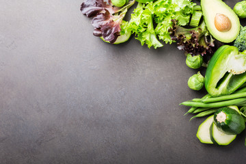 Background with assorted green vegetables, salad, broccoli, mini cucumber, peas and Brussels sprouts on brown stone table top. Healthy food concept with copy space.