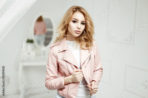 92bb7ef73 Beautiful blonde woman with curly hair in a fashionable pink leather ...