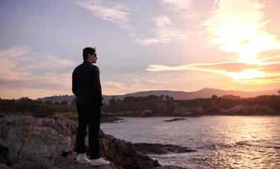 Hombre joven contemplando el atardecer ante el mar