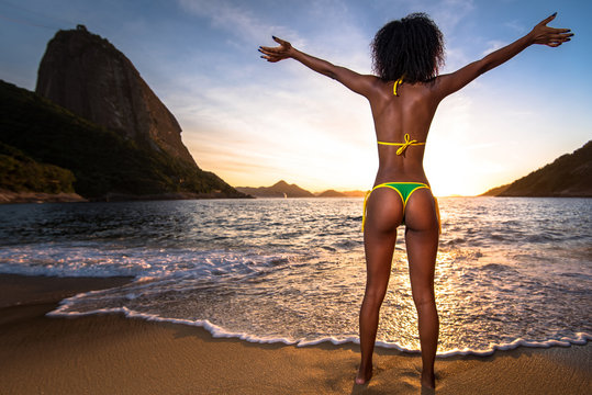 Sexy Brazilian Girl in Bikini Stands in the Beach With Open Arms and Welcomes A New Day in Rio de Janeiro With the Sugarloaf Mountain in the Background