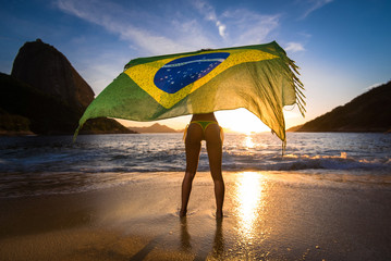 Sexy Girl in Bikini Holding Beach Yoke With Brazilian Flag Waving in the Wind, with the Sugarloaf Mountain View by Sunrise, in Rio de Janeiro